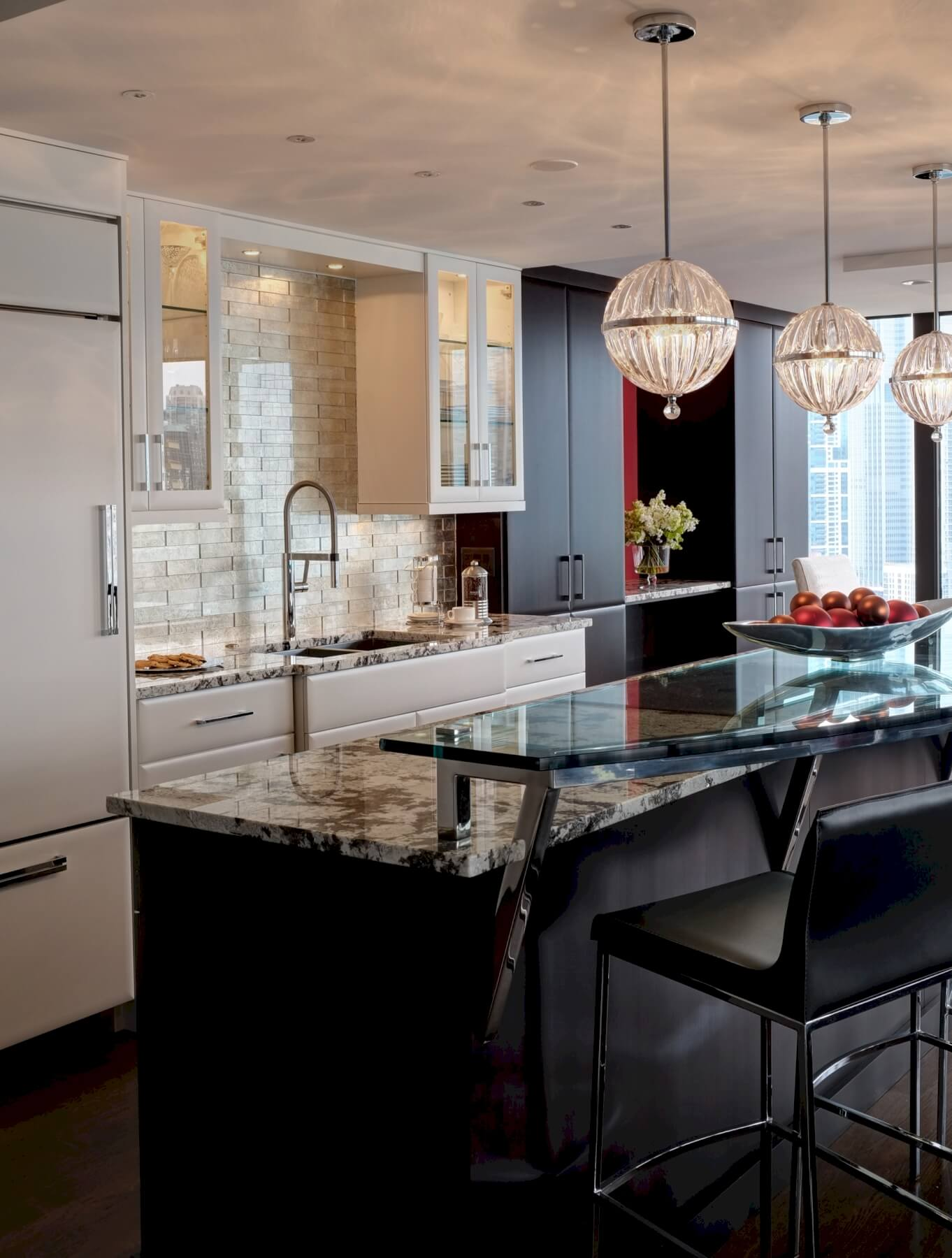 Intricate details abound here, including granite topped island with raised glass dinning bar, beige brick backsplash, and spherical chandeliers. Black and white cabinetry add visual contrast.
