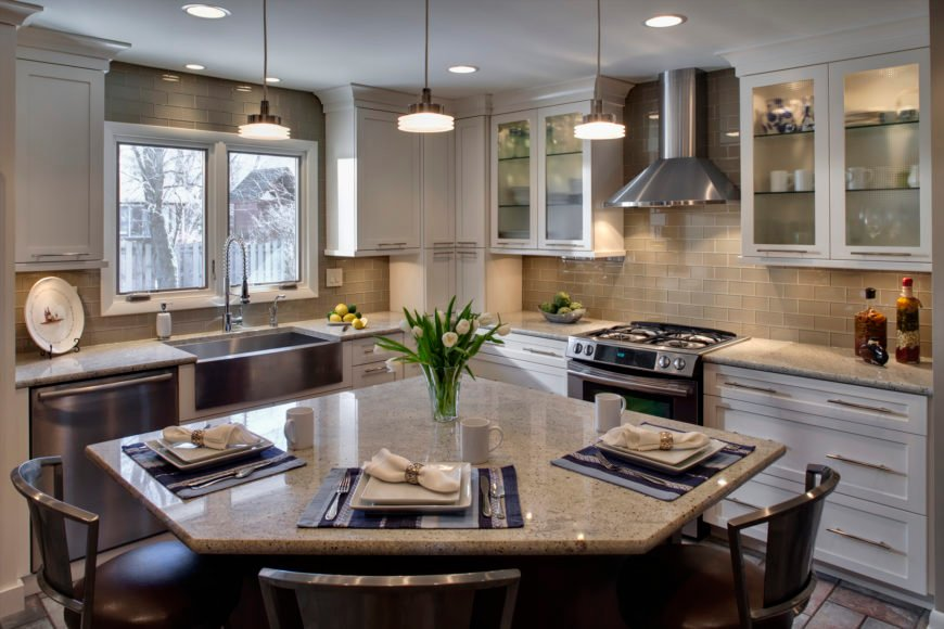 Another great example of tile backsplash paired with white cabinetry, this kitchen features a standout corner-cut island with granite countertop and seating for three.