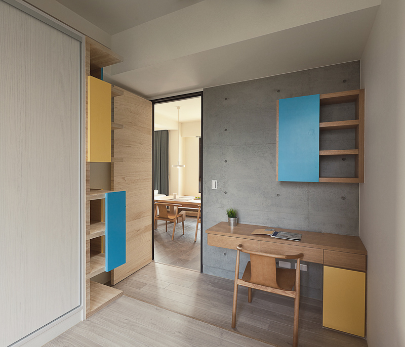 Cozy bedroom features visually exciting built-in wood furniture in a mixture of natural and bold color tones. Asymmetrical colored panels mount on shelving and corner desk really pop out amidst the neutral tones.