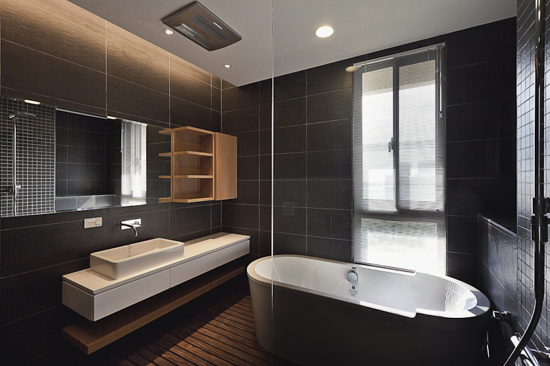 Bathroom stands out in the home, with darker tones courtesy of a stained hardwood flooring and large format wall tiles. Natural wood shelving and white vanity stand across from large pedestal tub in brown with white interior.