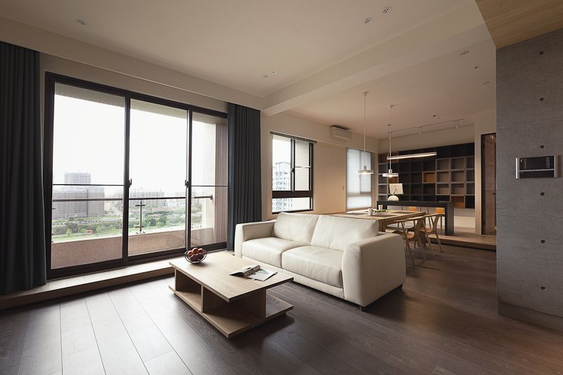 Plus white leather contemporary sofa defines the divide between living room and dining area in the large central open space. Concrete and white walls wrap the natural tones throughout.