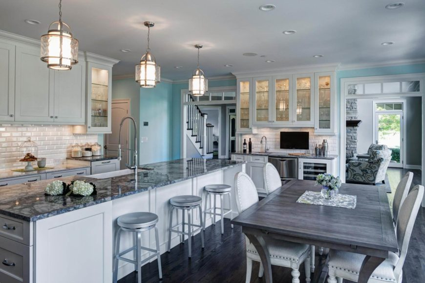 Bright, open design throughout this kitchen, standing white cabinetry and tile backsplash over dark hardwood flooring. Grey dining table and white chairs flip this contrast in reverse.