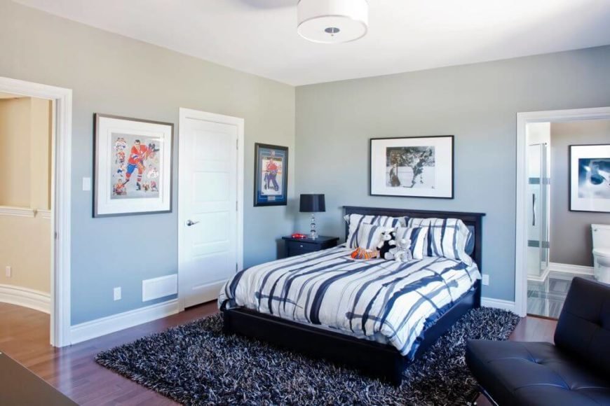 This bedroom suite features a large black wood frame bed over thick shag rug, contemporary black leather sofa, and bathroom access at right.