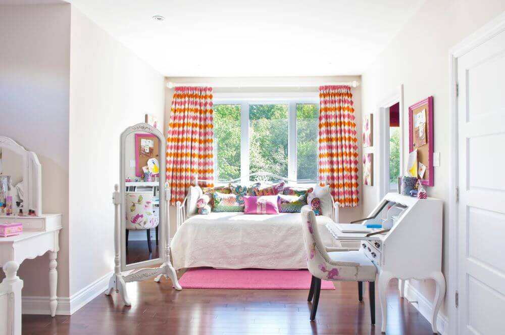 Wide view of the children's bedroom, showcasing array of white wood furniture, pink and orange accents, and lush hardwood flooring.