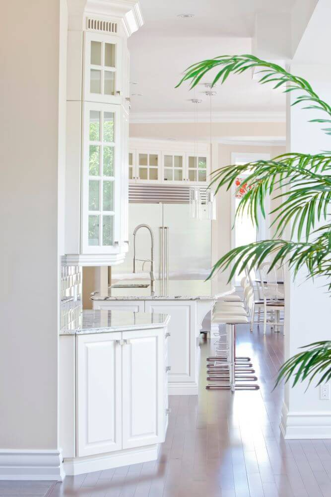 Looking down the length of the central space, past the kitchen, we see how light from the massive windows plays on the marble countertops, glass-door cabinetry, and steel appliances. Island features built-in sink and dining space, with a set of white and chrome bar stools.