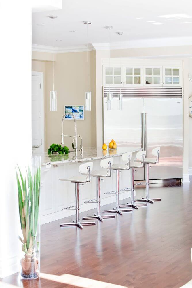 From the living room, we see the array of modern seating at the island, over more of the rich hardwood flooring. Massive steel refrigerator is topped with more glass-door cabinetry.