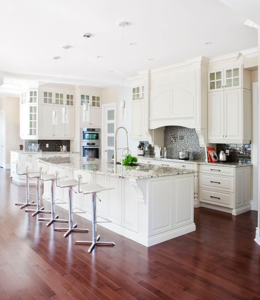 The complete kitchen pictured here. The mixture of white wood, dark hardwood flooring, marble countertops, and sharp tile accents creates a varied yet fluid look.