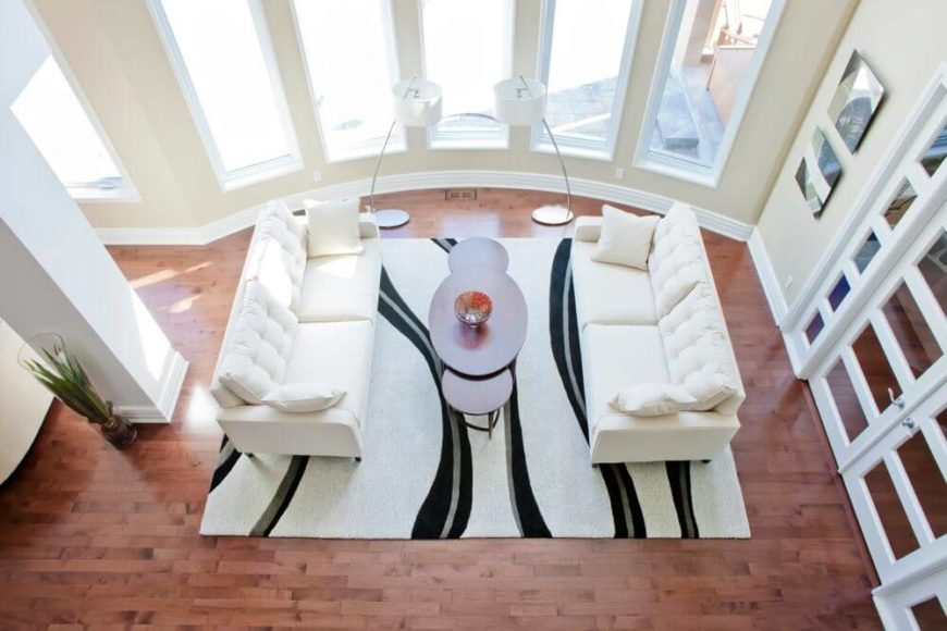 Looking directly down on the area, we see the rich, dark hardwood flooring extending throughout the home, into the adjacent room behind glass French doors.
