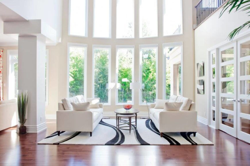 This seating area stands below a curved array of two story windows, for ultimate natural lighting. This raised ceiling space is shared with a more traditional, large open central space in the home.