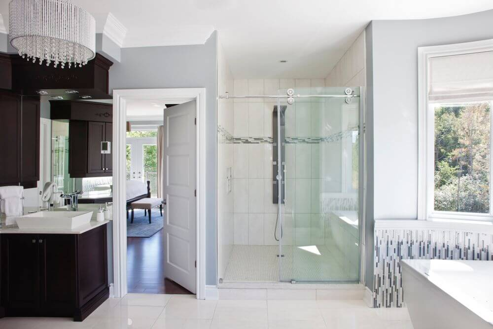 Wide view of the primary bath shows large shower area and dark wood cabinetry flanking bedroom access door.