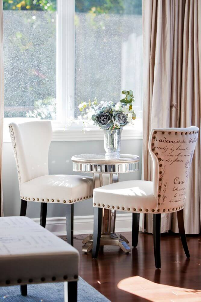 Small conversation seating area in bedroom holds these decorative accent chairs around a small mirrored table.