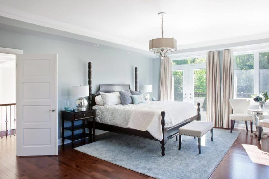 This bedroom features bed with dark wood frame, matching bedside tables, and small white cushioned bench over blue area rug, matching the light blue toned walls. Glass French patio doors stand in background.