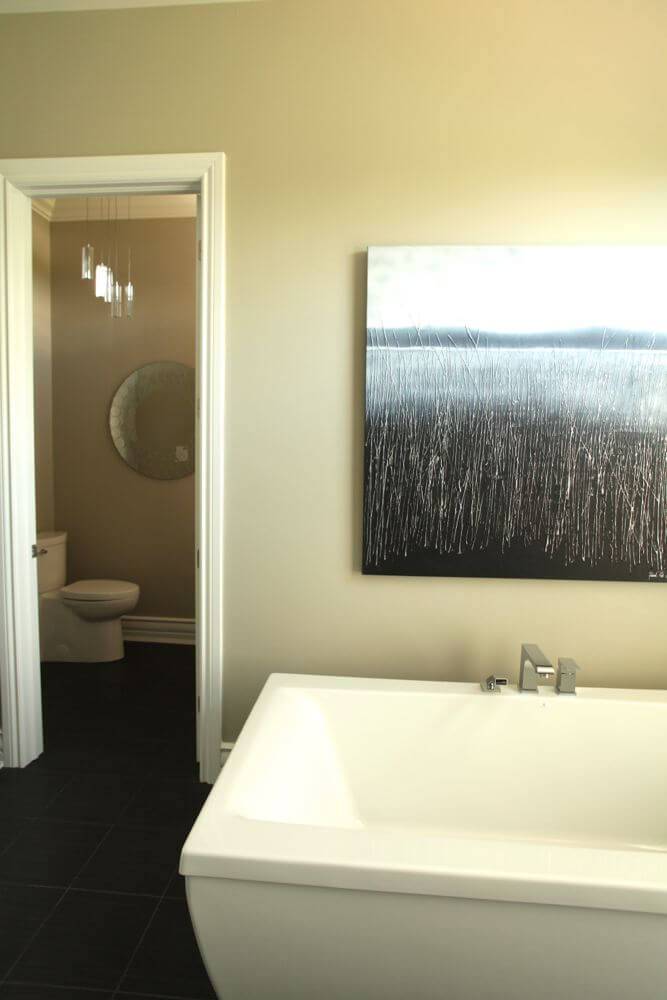 Large white pedestal tub beneath art print, with private toilet area on left.