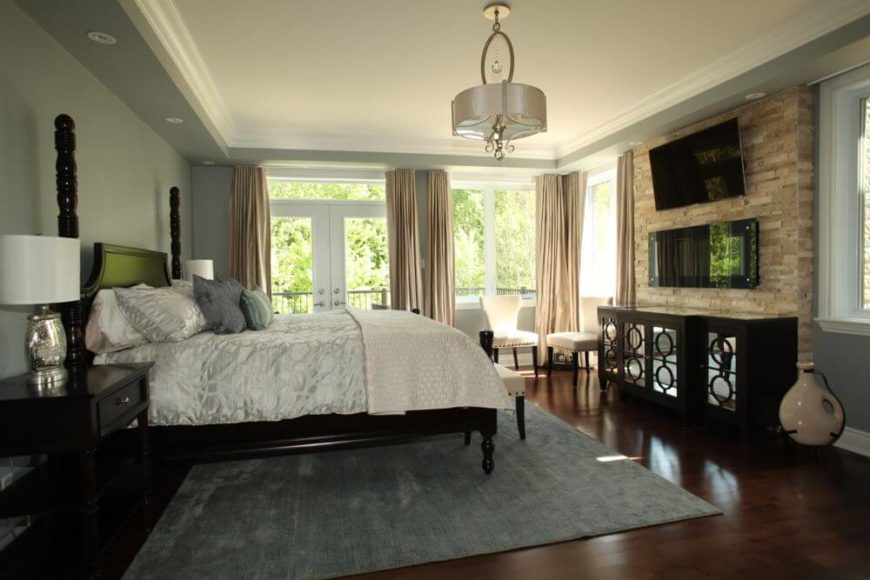 Primary bedroom places a singular brick wall between windows, holding gas fireplace, TV, and mirrored black wood cabinet across from the bed. Windows all around plus glass French doors naturally illuminate the space.