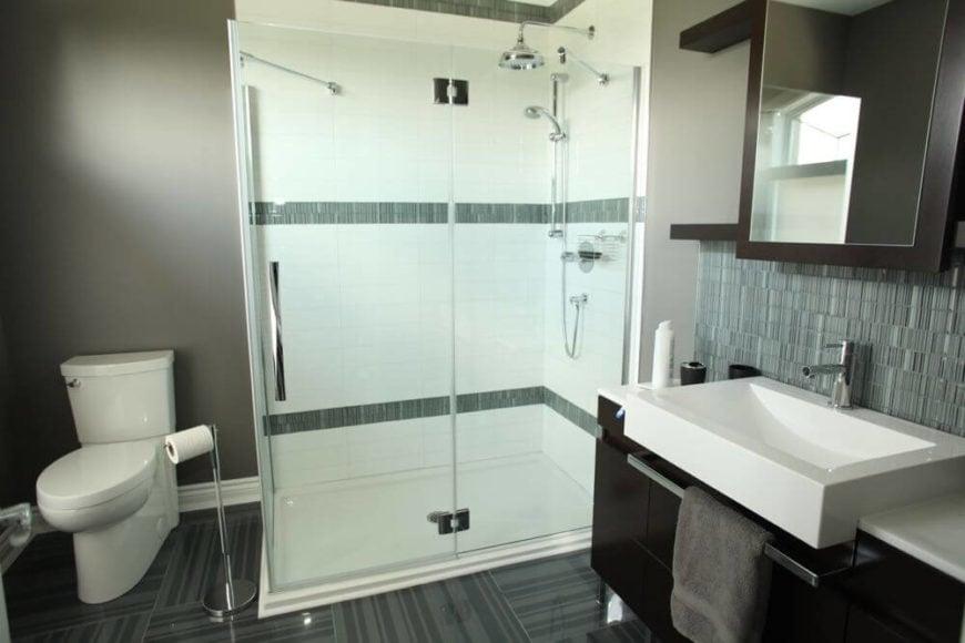 Another bathroom repeats the dark wood and vessel sink vanity design, with glass-door shower standing over blue stripe tile flooring.
