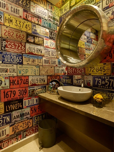 The striking, wildly colorful bathroom features license plate walls, with a metal cylinder mirror frame over marble countertop with white vessel sink.