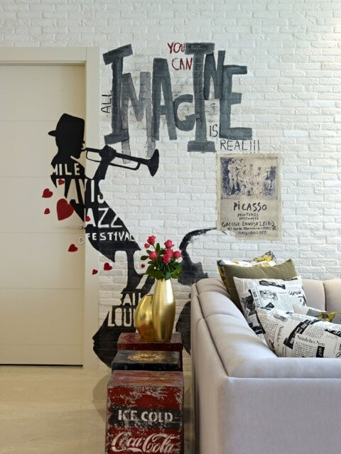"""The white brick walls hold numerous detailed personal touches, like this Miles Davis """"graffiti"""" and Picasso art print. The lush white sofa is populated with newsprint style throw pillows."""