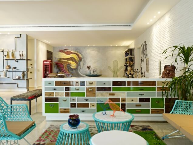 """In the """"greenery"""" space, various bright teal pieces of furniture stand over a patchwork rug, with the large dividing cabinet defining the area."""