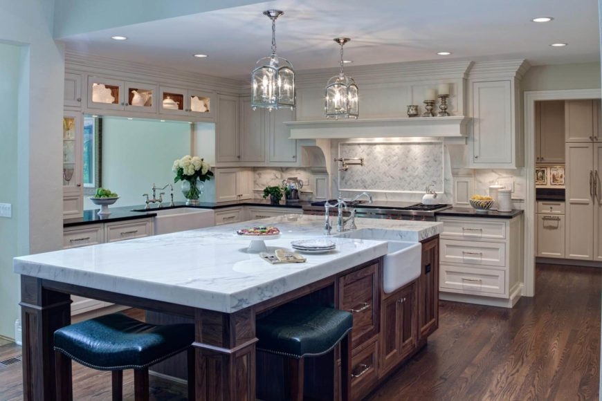 Immense dark wood island with thick slab marble countertop and built-in sink dominates this kitchen. White cabinetry, natural hardwood flooring, white tile backsplash, and living room pass-through fill out the space.