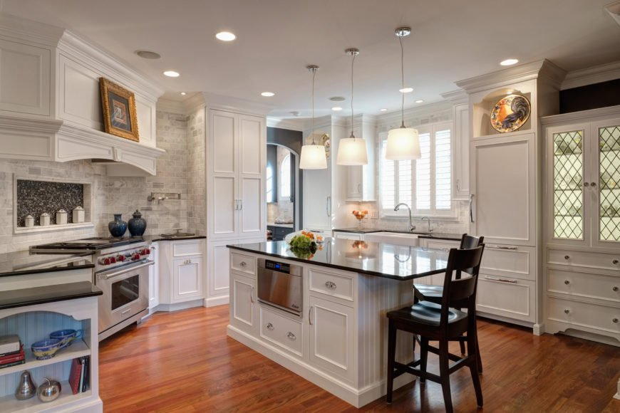 Transitional kitchen features carved wood white cabinetry doors, with modern steel appliances, black countertops, and an immense brick tile backsplash surrounding the range area.