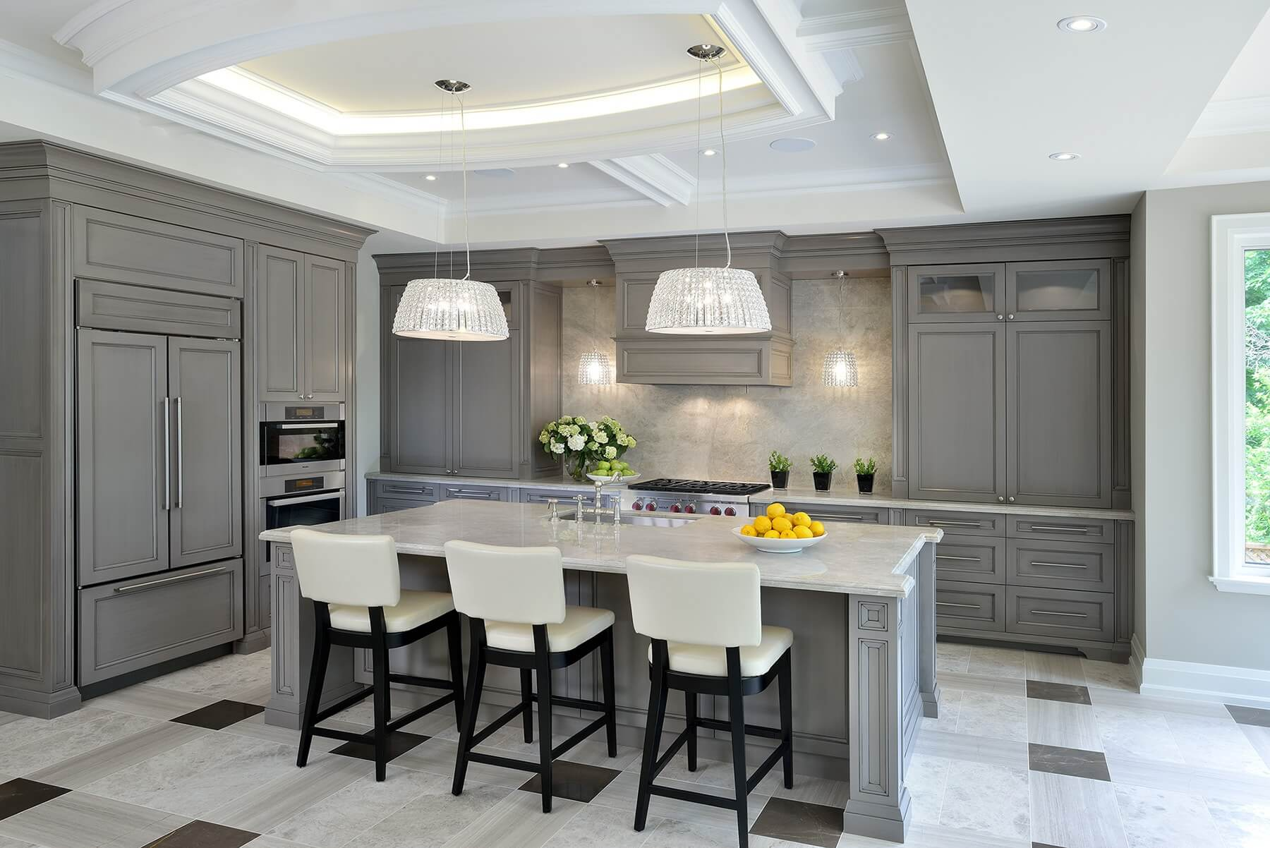 Large kitchen island features a polished quartzite countertop over custom grey cabinetry. Full height backsplash, seen behind crystalline chandeliers, is quartzite as well.