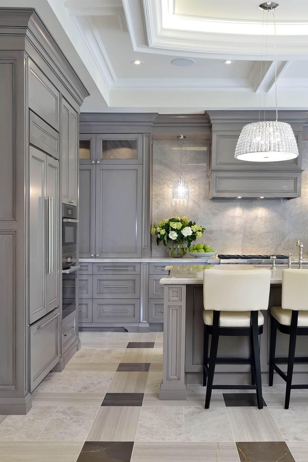 Here we have a closer look at the medley of light marble flooring, pairing sympathetically with the quartzite countertop and backsplash. Black frame, cream leather bar stools match the overall tone.