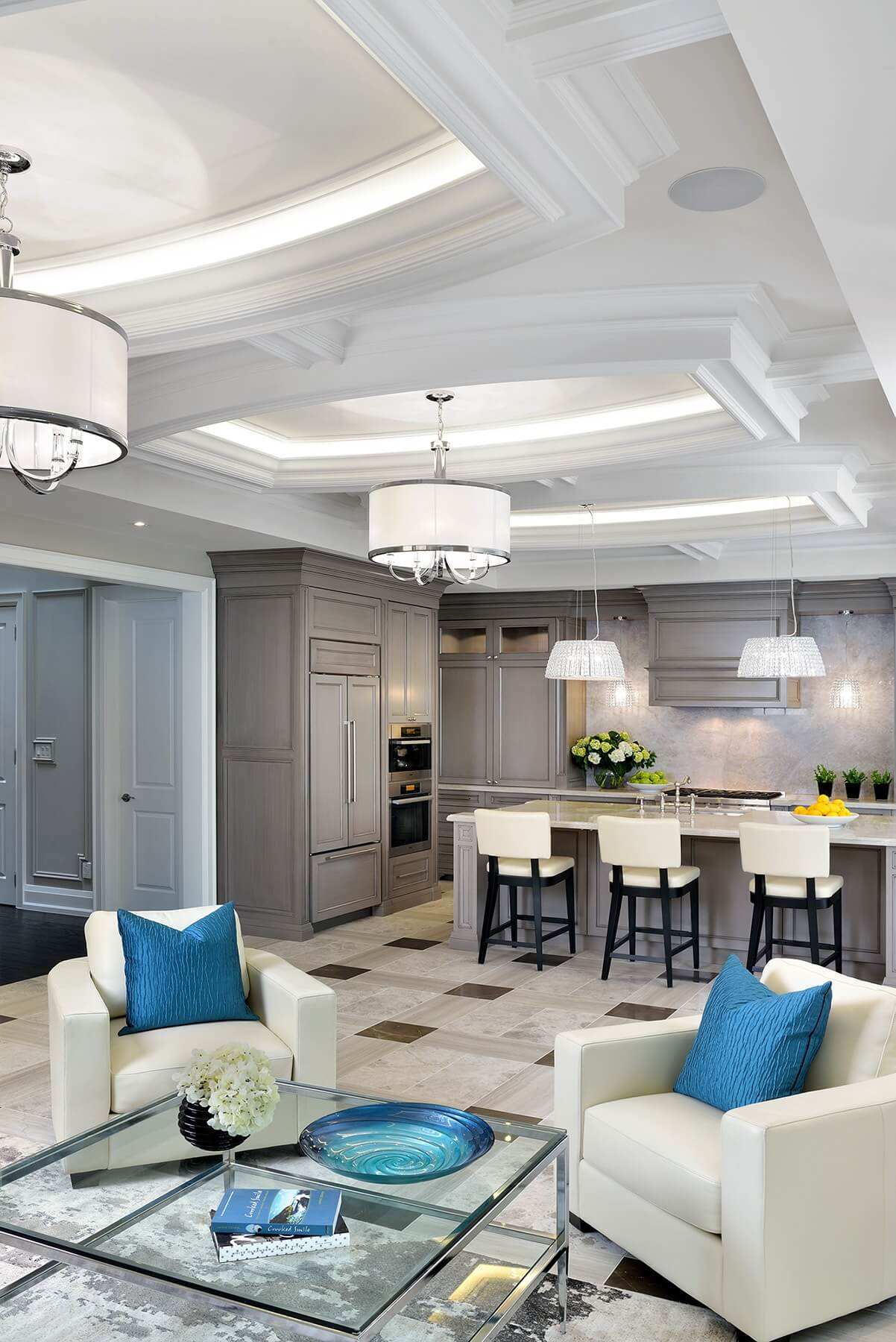 Central open space shares living room and kitchen, with an expanse of tile flooring pairing various shades of marble into an intricate pattern. White leather armchairs hold flashes of bold blue amidst the neutral theme.