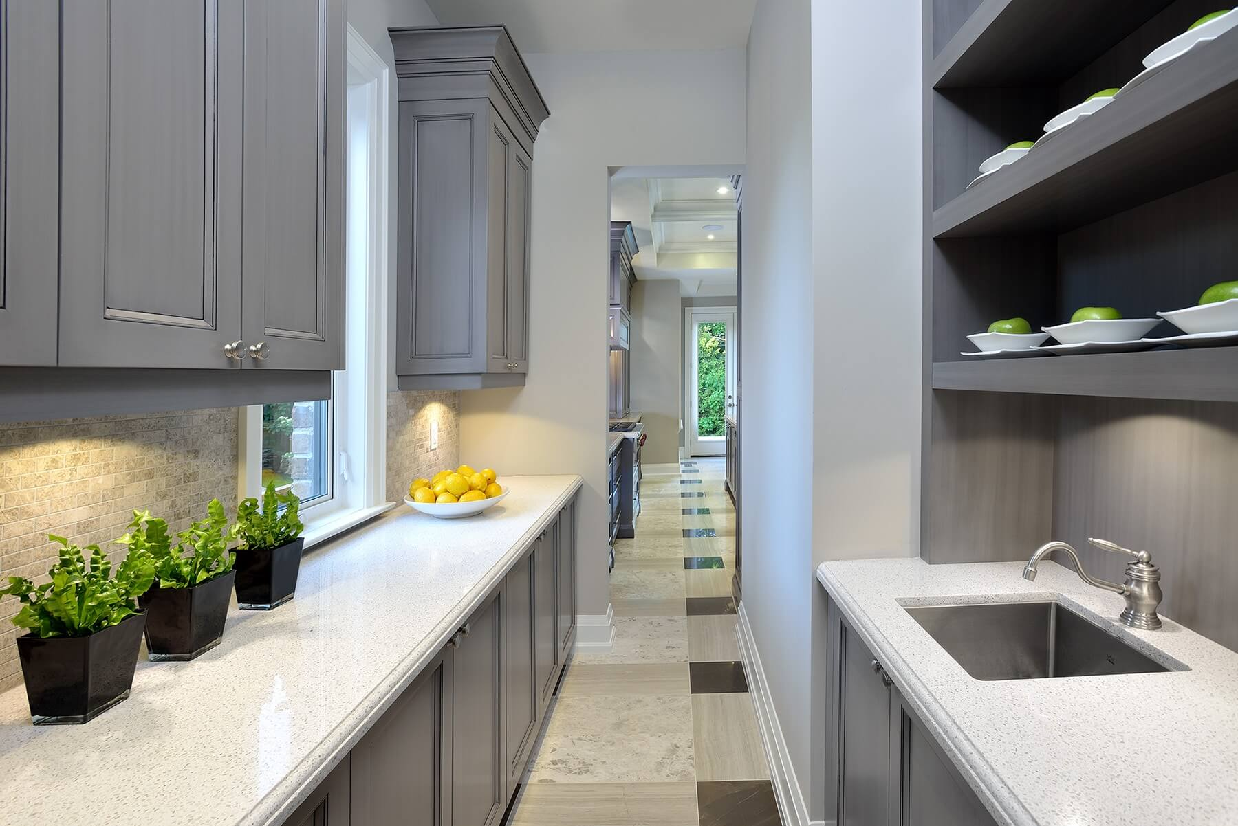 This hallway extending from the kitchen to the dining area functions as a pantry, with secondary sink and plenty of cabinetry.