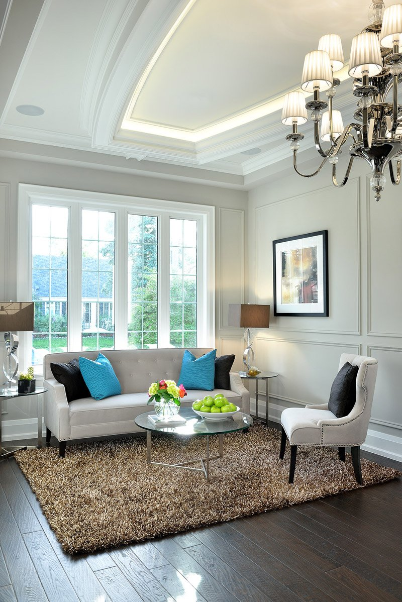 Cozy socializing corner stands soft grey sofa and chair, glass topped metal frame tables, and brown shag rug over rich, dark stained hardwood flooring.