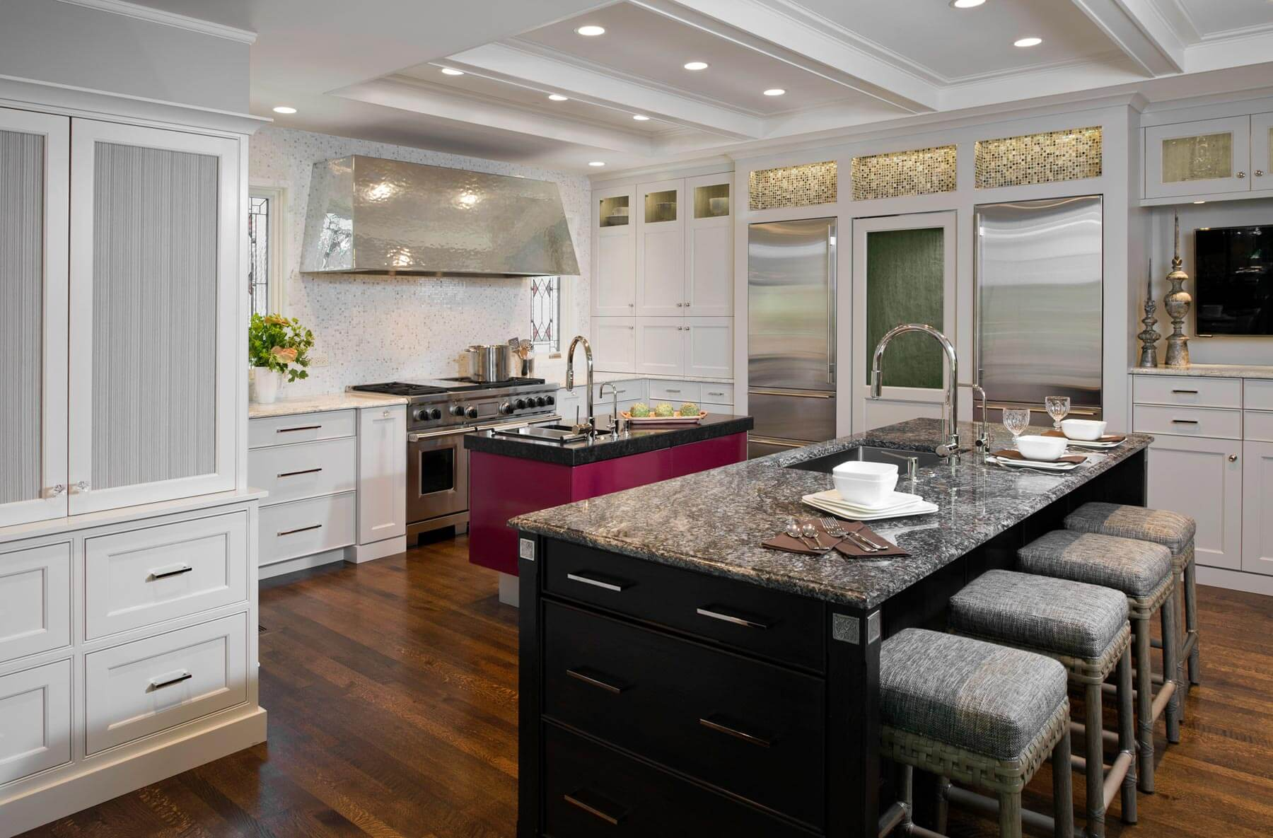 Modern open design kitchen features both an immense black wood island with granite countertop and a smaller magenta island with built-in sink and thick dark slab countertop. Steel appliances and white cabinetry surround.