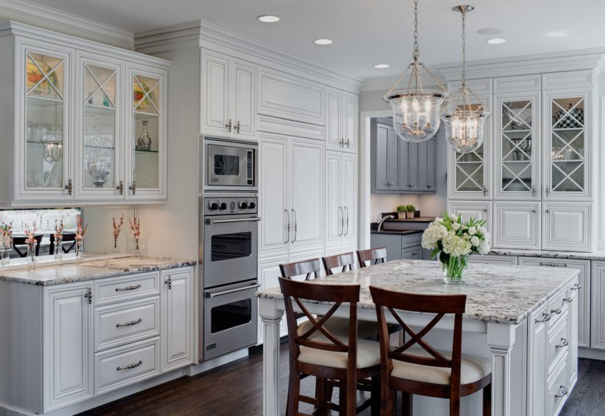 A more traditionally styled kitchen, featuring delicate details like the bell chandeliers and glass door cabinetry, over dark hardwood flooring. Large square island features an array of seating space.
