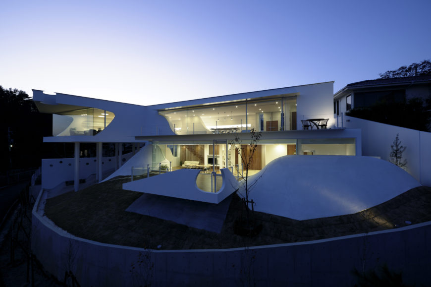 From an elevated perch, we see the full house in bloom at night, with the sloping and angular structures wrapped around expanses of illuminated glass.