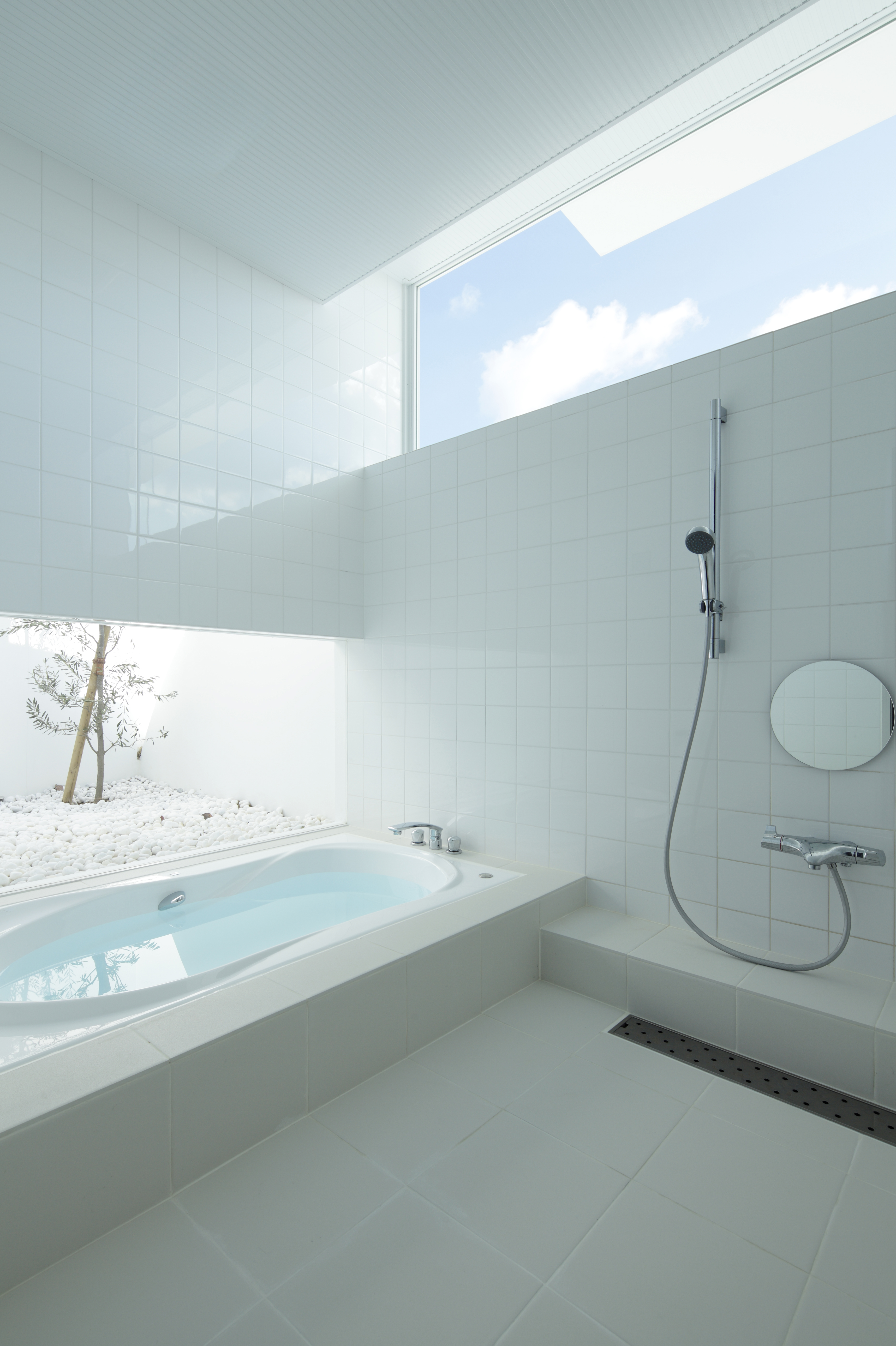 The bathroom is a striking, pristine expanse of white tile and sunlight, with open design shower next to jacuzzi tub, with exterior white rock garden seen through lower window at left.