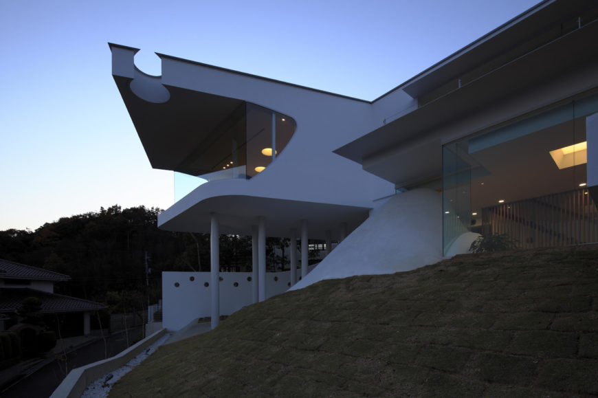 From this angle, we see how the home rises from the hillside itself, organically curving into stark, angular shapes at the extremes.