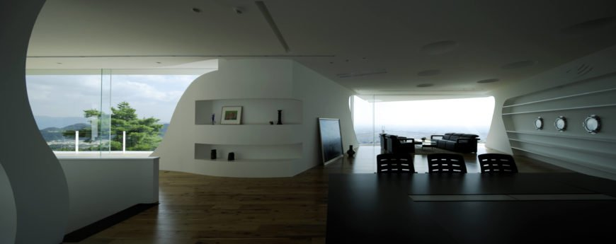 Port hole windows - another Easter Design Office hallmark - stand out on the shelving-lined wall at right. From across the open living space, we see the striking views available.