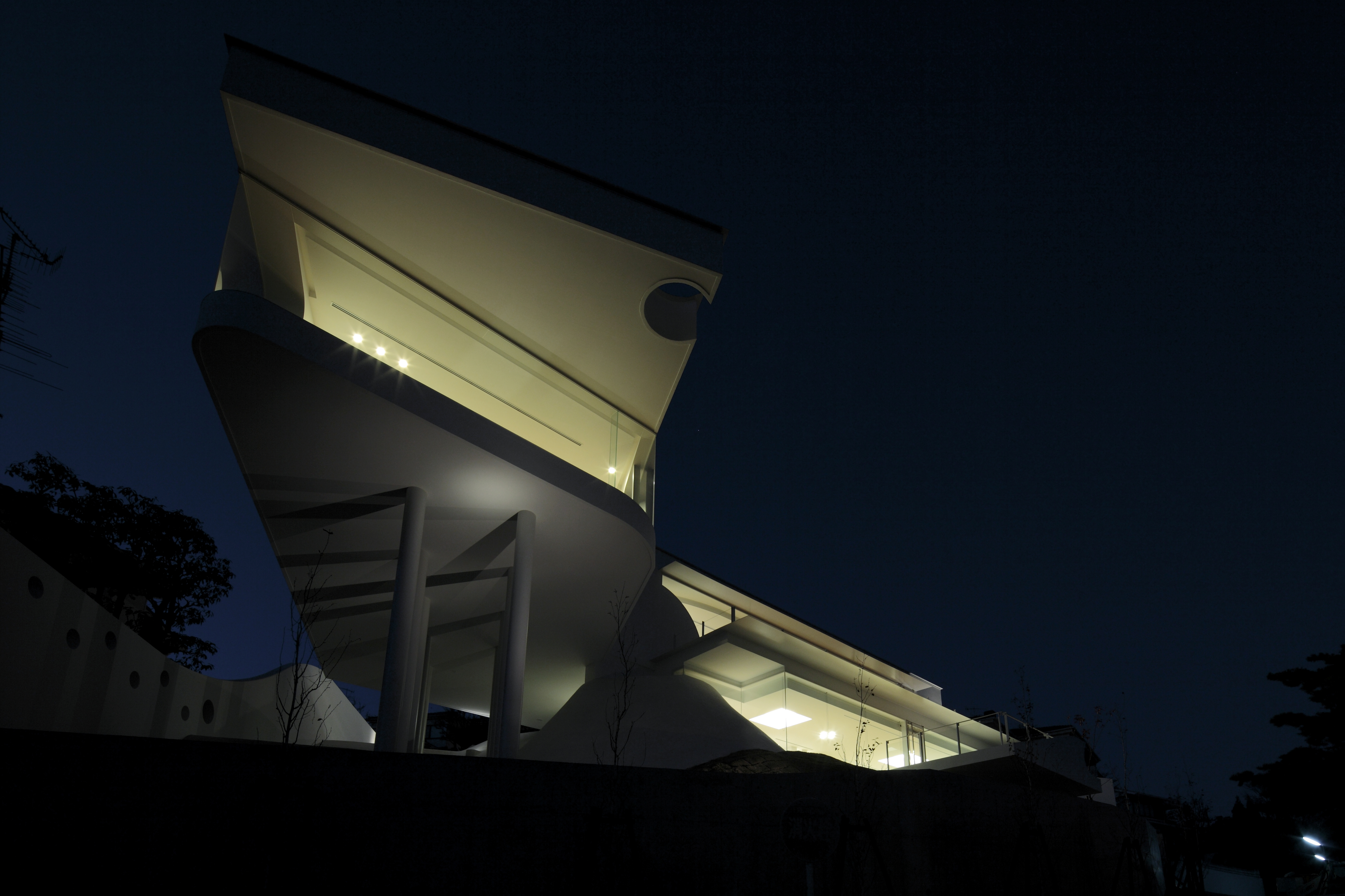 Looking up at the home at night, glowing from below and appearing to extend from the ground itself.