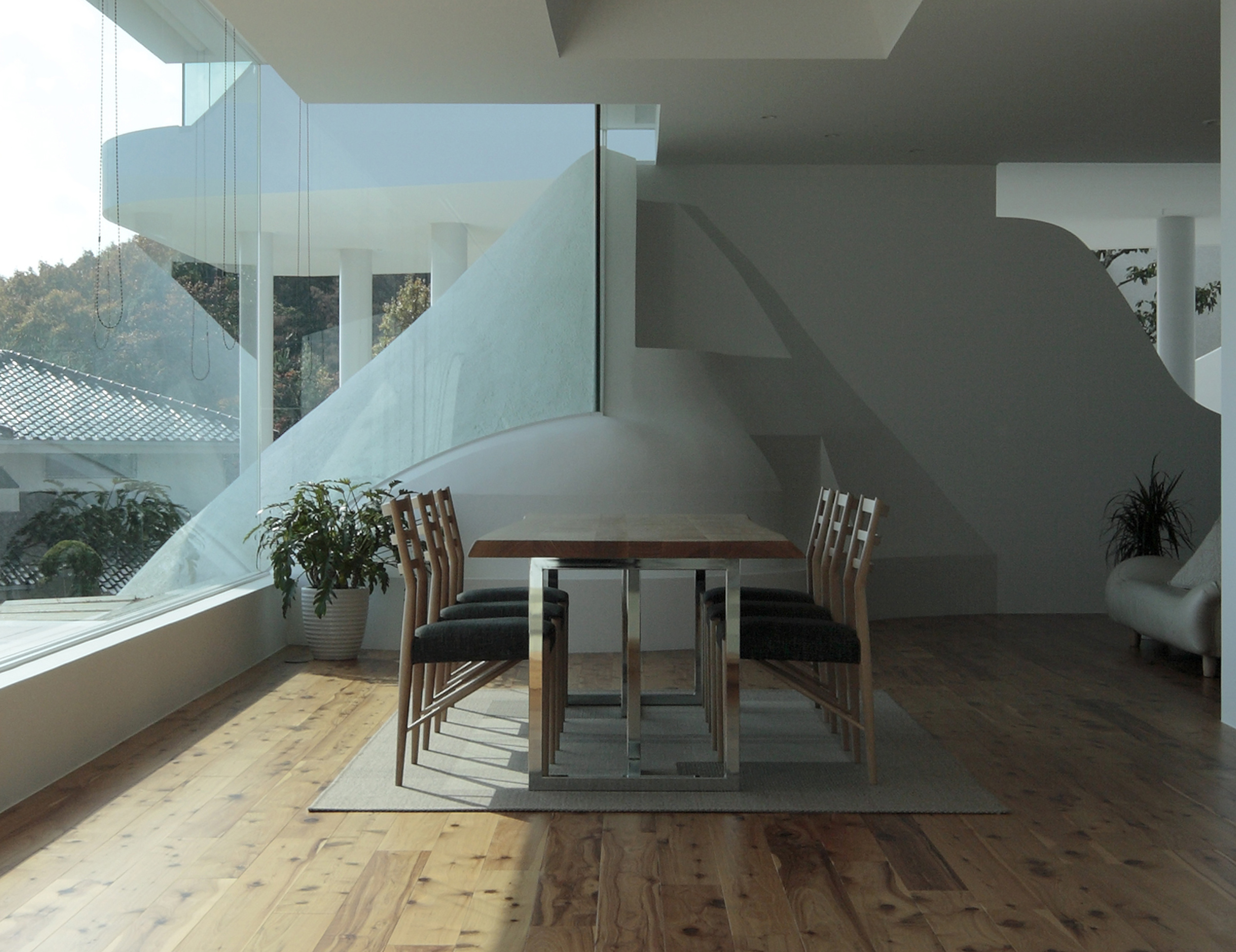 Dining table, in metal frame and carved wood surface, stands next to the immense floor to ceiling glass, overlooking spectacular views from this lower level of the home.