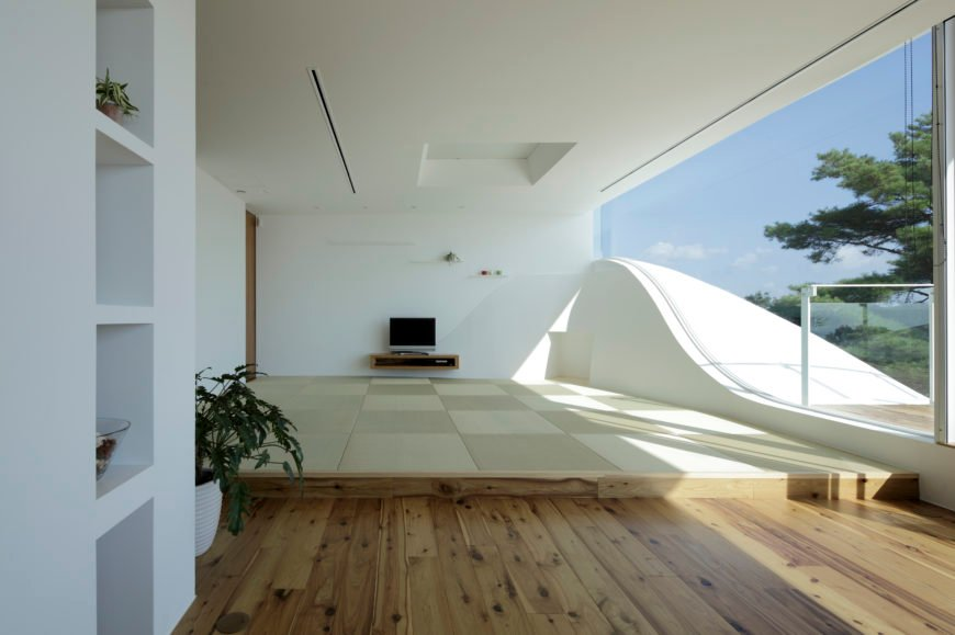 Sharply minimalist living room stands on a raised floor above the surrounding hardwood, with full height glass following the structural slope at right. Small entertainment shelf stands below carved wall with built-in stepped shelving.