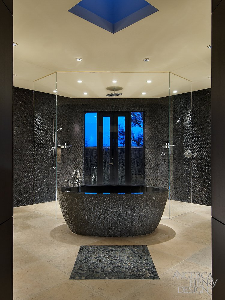 Primary bath features this carved granite pedestal tub at center, with a massive, all-glass shower backdrop.