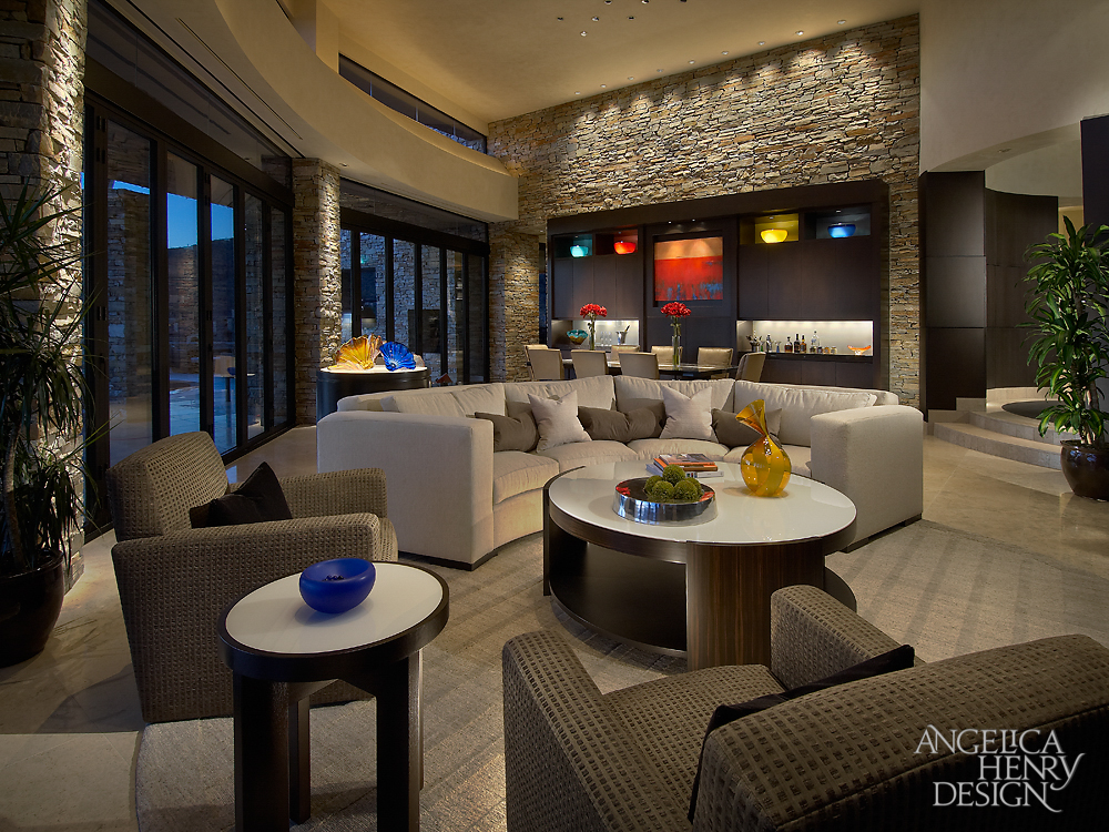 Living room features stone brick walls and full height glass panels surrounding curved beige sofa, armchairs, and circular tables, with dark rift cut oak cabinetry and wet bar in background by dining table.