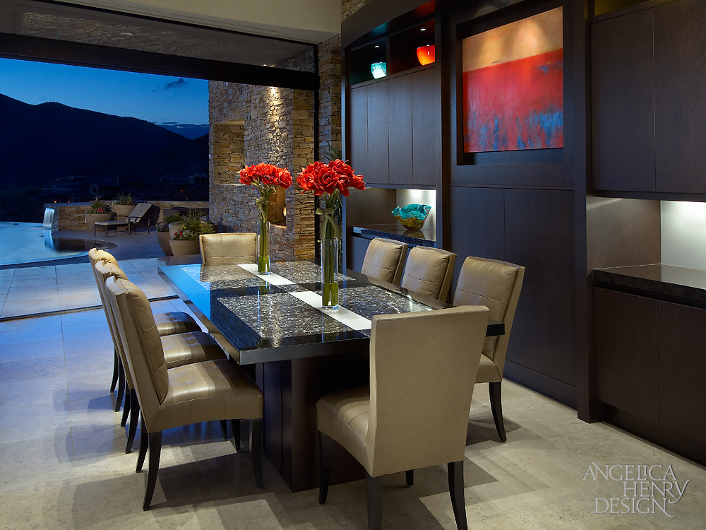 Custom dark wood and granite dining table stands before a wide open expanse toward the patio, courtesy of folding glass panels. The dark oak cabinetry with small bar stands at right.
