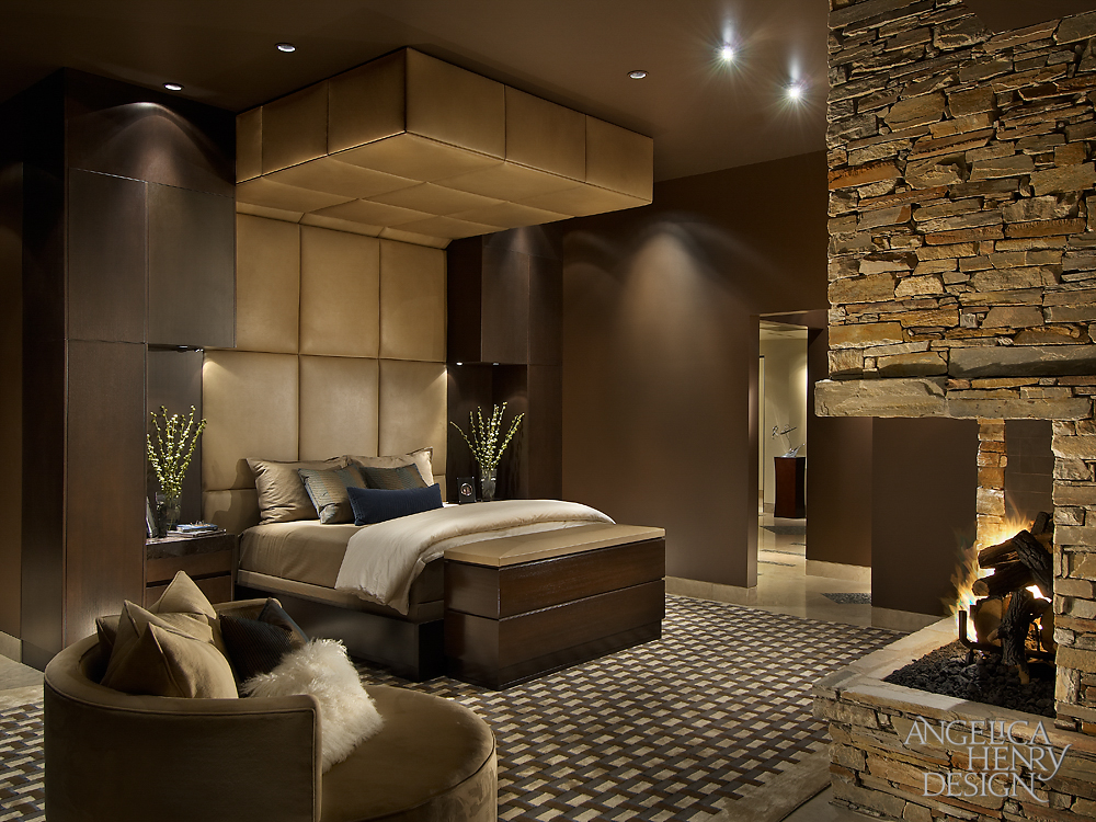 Primary bedroom features a bed surrounded by an immense upholstered headboard and soffit, with a custom television lift at the foot. Stone corner fireplace stands across patterned rug, with custom circular armchair in corner.