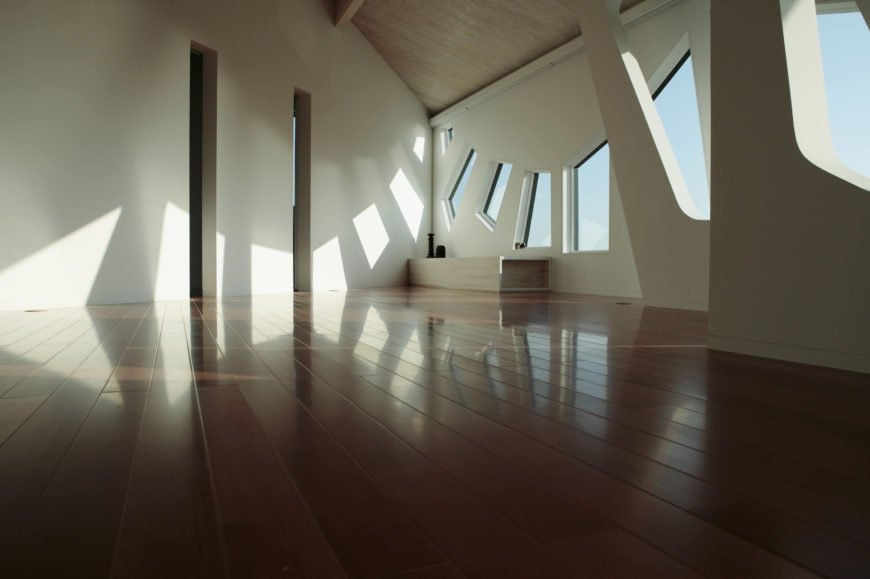 Moving inside, we see the lush natural hardwood flooring, naturally lit beneath the polygonal windows on white walls.