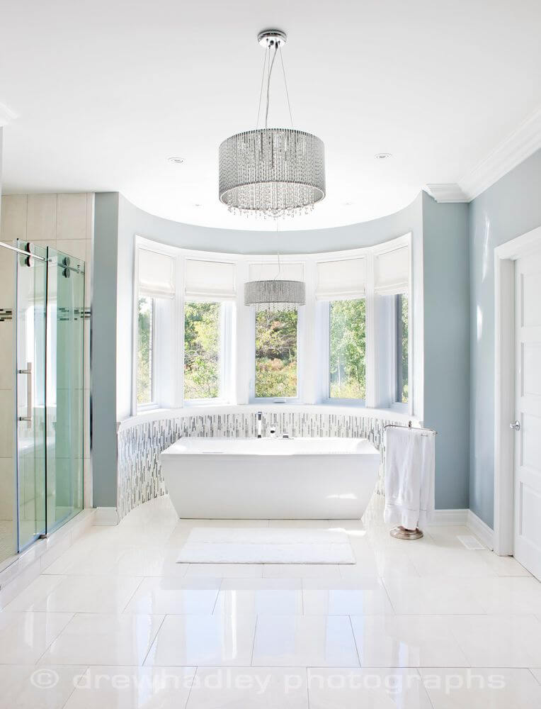 Primary bath is awash in pristine white tile, with pedestal tub standing in curved window area next to sliding glass door shower.
