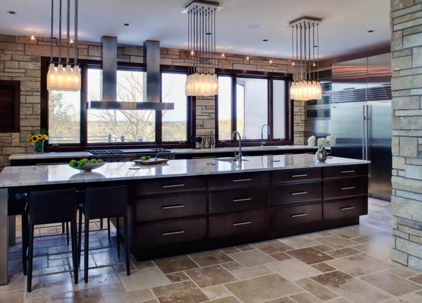 Stone walls wrap this open kitchen, featuring an immense dark wood island full of storage space and a complete 4 seat dining area. Intricate column chandeliers hang above brown tile flooring before an expanse of windows.