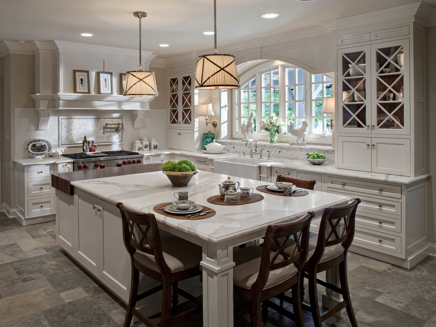 Wide open design allows this white kitchen to stand an immense marble topped island at center with wide stretches of tile flooring all around. Island features partial hardwood surface, while sink space and tile backsplash sit below a wide arched window.