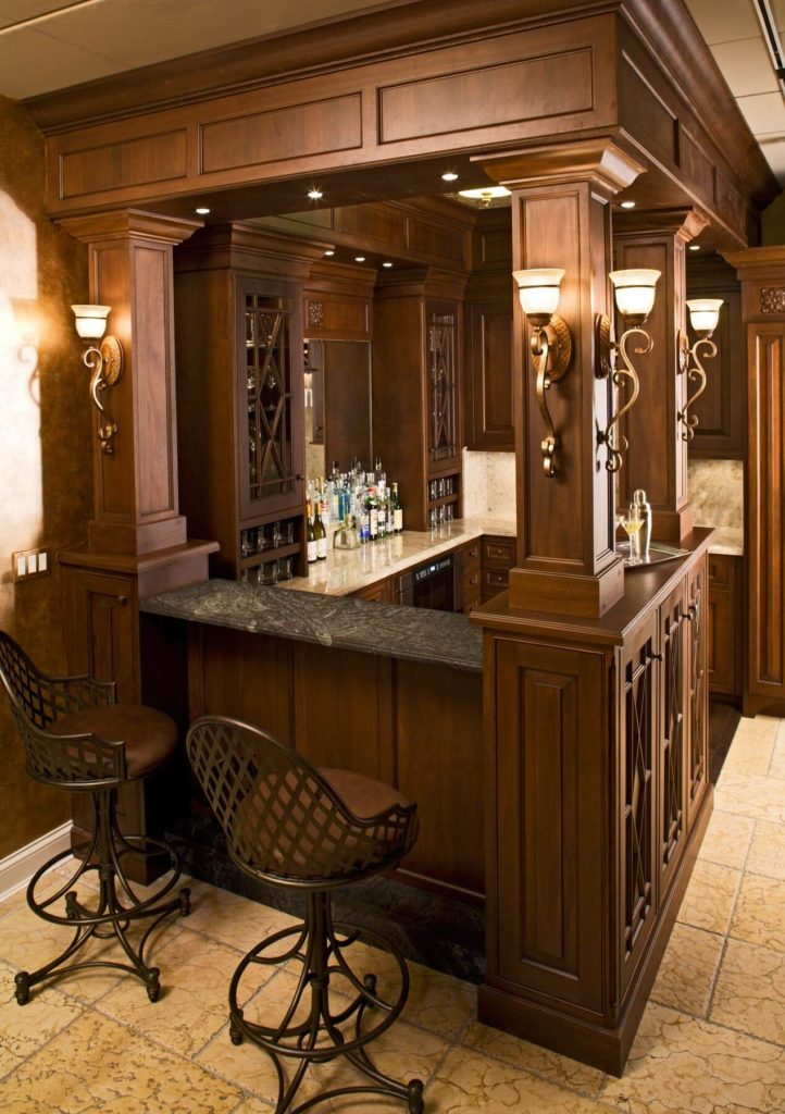 This bar features a classy counter lighted by elegant wall lights. The tiles flooring looks stunning as well.