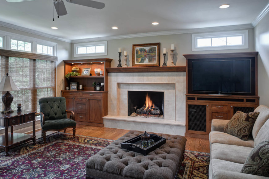 A large marble framed fireplace dominates this room, with a light wood mantle connecting a pair of flanking wood cabinetry sets. Natural hardwood flooring spreads beneath a large patterned area rug, with immense button tufted ottoman at center, while wood framed chair and carved table stand below full height windows at left by Drury Design.