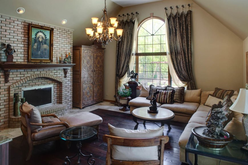 Bespoke luxury informs this cozy family room, framing a rich hardwood floor with tile all around. Large brick fireplace with carved wood mantle commands attention, while an old fashioned chandelier hangs at center in view of an arched, full height window. L-shaped sectional balances a pair of wood framed chairs and circular coffee tables.