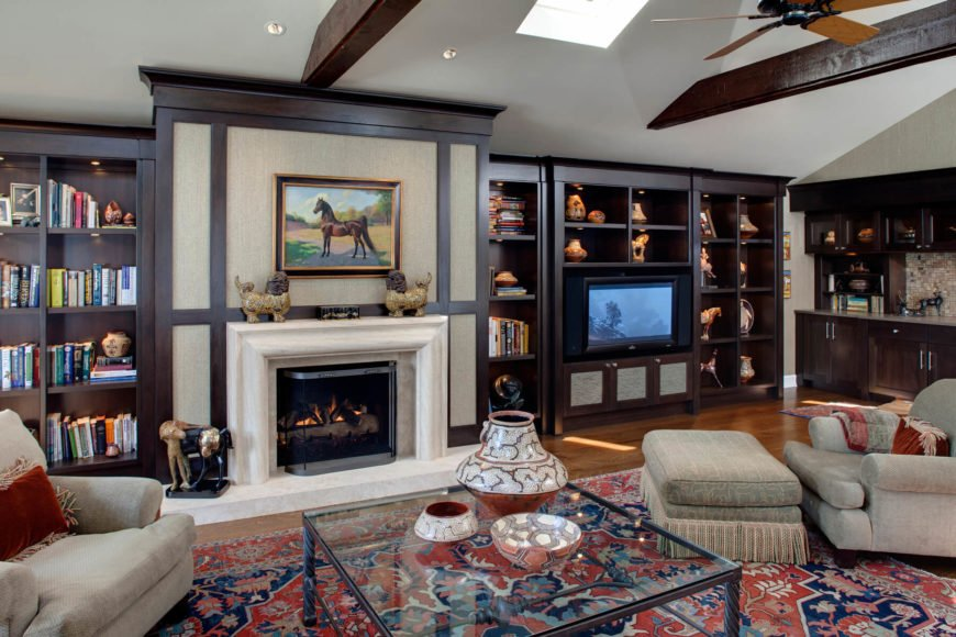 This vaulted ceiling family room features a room-length rich oak cabinetry set surrounding a bold, marble wrapped fireplace beneath rich exposed wood beams. Red and blue patterned area rug over hardwood flooring supports rolled arm seating and a large metal and glass coffee table.